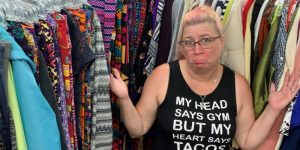 woman selecting used clothes wearing a clever shirt